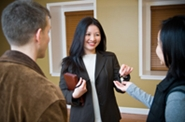 realtor handing keys to new home to newly married couple